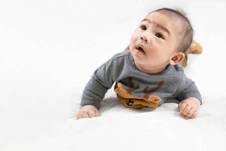 Adorable newborn kid during tummy time smiling happily at home.Portrait of cute smiling happy asian baby boy crawling on bed on the white blanket in bedroom.