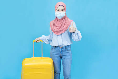 Young asian muslim woman in traditional dress wearing medical face mask holding yellow luggage or suitcase isolated over blue background,travel concept Standard-Bild