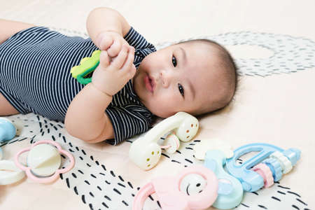 Adorable smiling happy asian baby boy having fun with toys on play mat. Happy healthy kid playing on floor with mobile educational toys. lifestyle concept. authentic childhood Standard-Bild