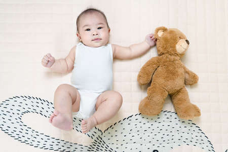 Asian baby healthy boy lying with bear toy on play blanket at home.