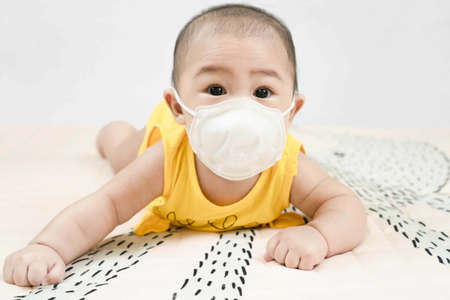 Little baby in medical mask lying on bed at home.Concept covid-19 coronavirus pandemic. Child wearing face mask protect from infection of virus outbreak disease on quarantine.