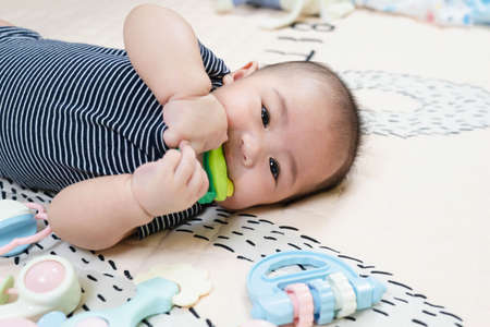 Asian baby four or five months old having teeth growing issues teething pain while holding a bite toy looking to the camera lying on the bed with teether at home Standard-Bild