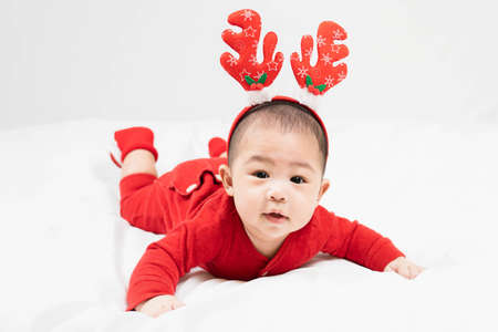 New year and Christmas concept with 5 months old cute asian newborn baby boy wearing christmas antlers of a deer,red clothes laying on the floor at home.Gifts for kids. Holiday season.