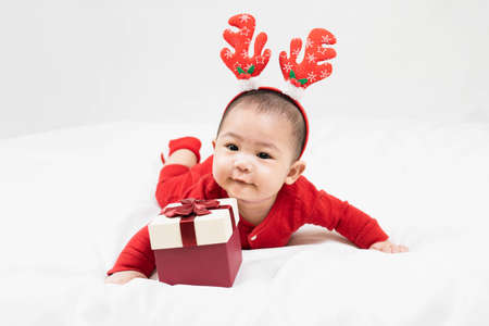 New year and Christmas concept with 5 months old cute asian newborn baby boy wearing christmas antlers of a deer,red clothes laying on the floor with gift box at home.Gifts for kids. Holiday season.