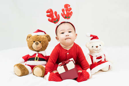 New year and Christmas concept with 5 months old cute newborn baby boy wearing christmas antlers of a deer,red clothes sitting on the floor with santa teddy bear.Gifts for kids. Holiday season Standard-Bild