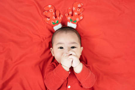 Headshot of 6 months old cute newborn baby boy wearing christmas antlers of a deer on a red blanket.Looking at camera. Holiday season. Standard-Bild