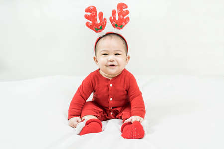 New year and Christmas concept with 5 months old cute newborn baby boy wearing christmas antlers of a deer,red clothes sitting on the floor at home.Smiling and looking at camera. Holiday season