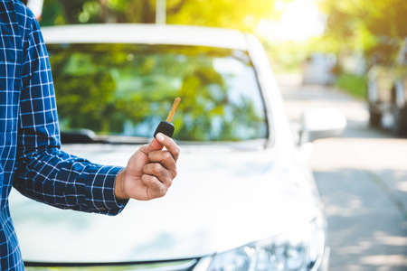 Hand man getting his key outside car. Concept of rent car or buying car. Stock Photo