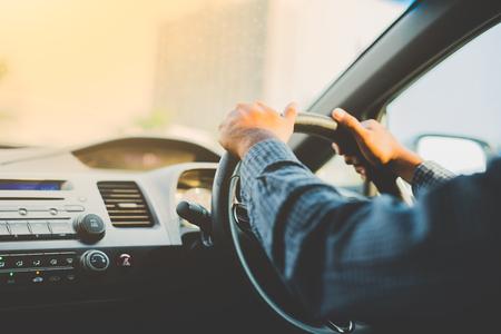 Mani maschio alla guida della sua auto.