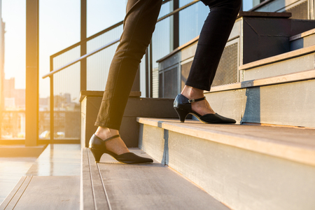 Business woman up the stairs. Female legs in high heels shoes walking on the stairs. Stock Photo
