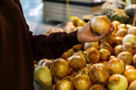 Women hand pick up onion in supermarket.