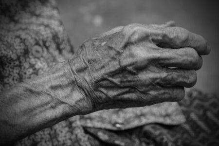 Handen van de oude vrouw. Zwart en wit.