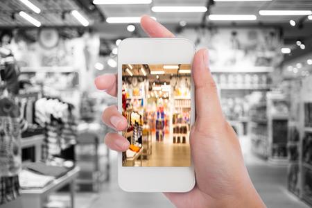 compras: Las mujeres en el centro comercial que usa el teléfono móvil.
