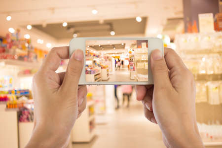 picture person: Taking a picture with a smart phone in shopping mall.