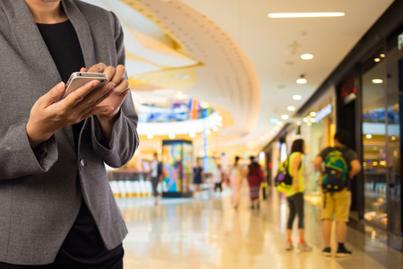 retail: Women in shopping mall using mobile phone. Stock Photo