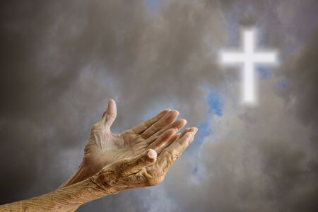 spiritual background: Hands of senior woman praying over blurred the cross on the sky background.