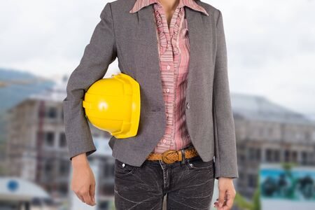 security helmet: Engineer holding yellow helmet for workers security on background Stock Photo