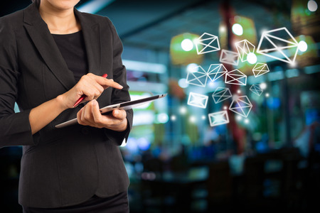 conection: Business woman sending email by using digital tablet