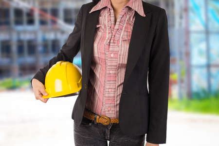 construction project: Engineer holding yellow helmet for workers security on background Stock Photo