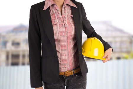 yellow helmet: Engineer holding yellow helmet for workers security on background Stock Photo