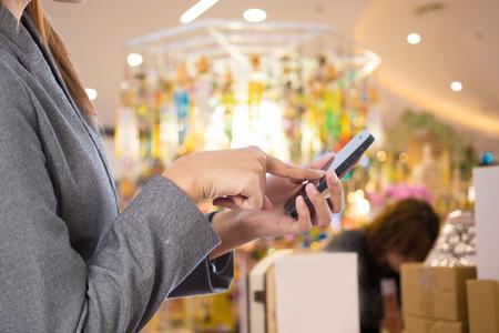 retail shopping: Women in shopping mall using mobile phone. Stock Photo