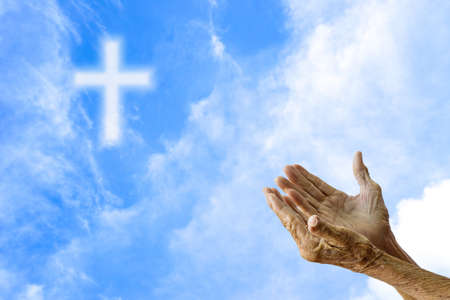 mujeres orando: Manos de la mujer mayor que ruega sobre borrosa la cruz en el cielo.