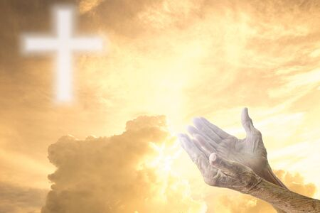 sky: Hands of senior women praying over blurred the cross on the sky.