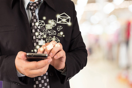 conection: Business man sending email by using mobile phone.