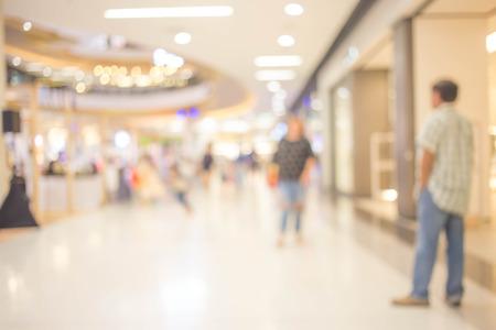 Personas en movimiento en escaleras mecánicas en el moderno centro comercial.