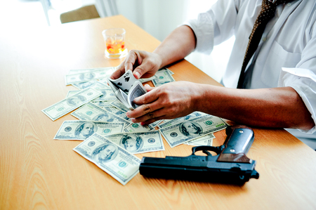 Businessmen with money in hand, US dollars, investment, success and profitable business ideas. Businessman with a firearm.