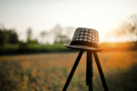 A young man's hat is placed on a tripod. With sunset in the evening Splash And beautiful