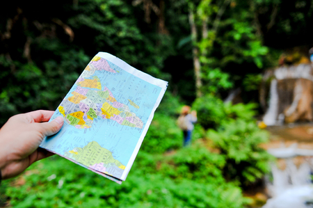 A tourist and his map on a trip to the forest in Thailand. Rich with pastures and streams. Banco de Imagens