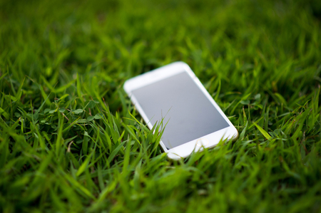 cellphone Placed in a light green grass. Every phone must have a home. Phone Concept