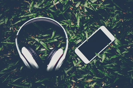 Hands and headphones are placed next to each other in green grass and moody music. Concepts of communication and listening.