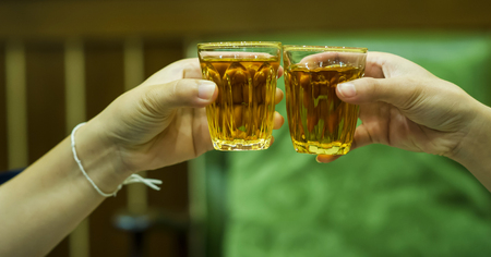 Hand and liquor juices in the liquor store drinking liquor. The concept of drinking and intoxication