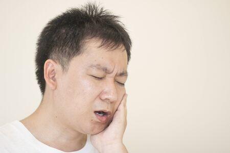 Colpo al coperto di un giovane maschio che sente dolore, che si tiene la guancia con la mano, soffre di un forte mal di denti. Concetto sanitario e medico. Archivio Fotografico