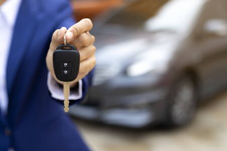 Close up of dealer giving key to new owner and shaking hands in auto show.auto business, car sale, deal,concept Stock Photo