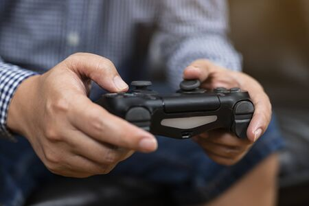 Close up hands of man holding console playing the video game at home.playful enjoyment view concept.