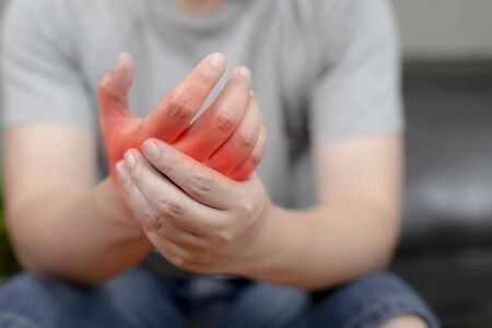 A young man with pain in his hand because of hard work, Ache in human body , office syndrome,Bone and joint disease, Concept healthcare and medical.