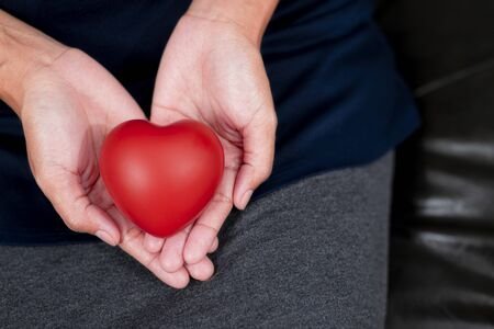 Woman's hand holding red heart shape. Heart disease concept and  love concept.