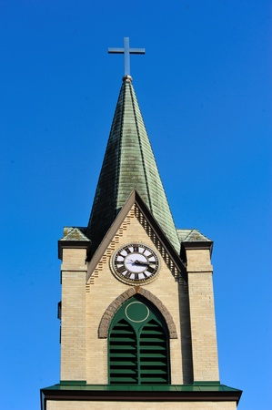 Beautiful Church Steeple With Clock Against Blue Sky Background in Westfield, Wisconsin