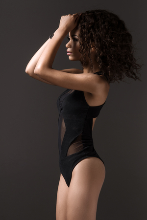 Afro sexy woman posing in black lingerie, looking at camera.