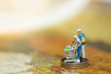 madre tierra: Miniature people : Family Mother, Father and children shopping  buying around the world with cart on stack of coins, spending money concept