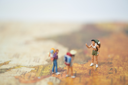miniature people travelers with backpack standing on a word stock