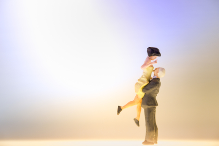 Miniature couple dancing or standing on the shining floor,Love and date concept with copy space