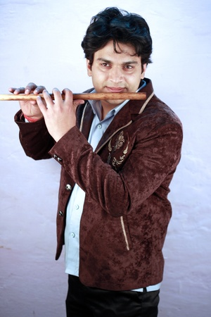 agrassive: yong indian male model playing flute