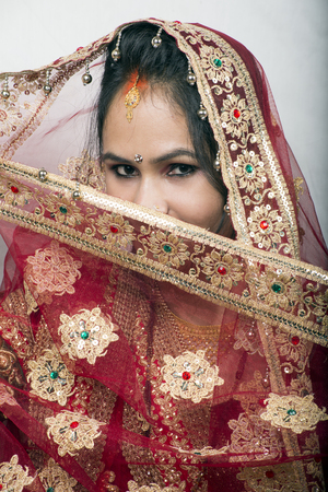 indian bride posing half face holding chunari