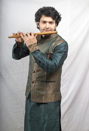 kurta: indian model in green kurta playing flute