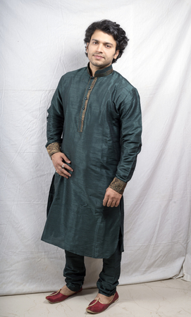 kurta: indian male model in green traditional kurta front pose