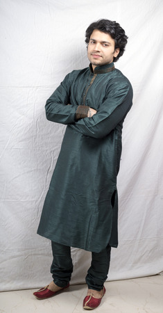indian male model in green kurta holding hands side pose